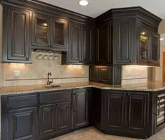 Furniture , Suave Distressed Black Kitchen Cabinets : Distressed Black Kitchen Cabinets With Round Sink And Bronze Faucet And Glass Wine Rack And Granite Countertop