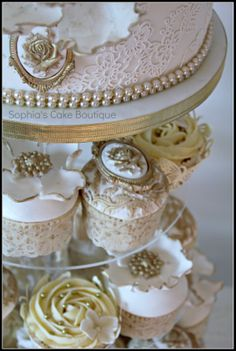 Rococo Cupcakes - A collection of elaborate Rococo inspired gold and ivory fondant wedding cupcakes with edible sugar brooches  flowers hand painted with gold lustre finished with genuine victorian antique lace. They accompanied a two tier wedding cake in a cupcake tower.