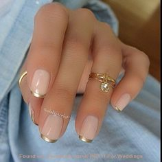 Gold trim version of a french manicure .