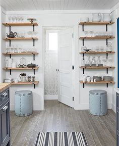 Tracery Interiors - Amazing kitchen features a beadboard ceiling over walls painted Benjamin Moore White Dove lined with stacked wood shelves with cast iron brackets alongside two Lee Industries Drum Stools alongside a Dash & Albert Birmingham Black Indoor Outdoor Rug.