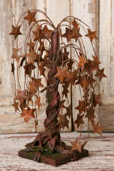 """18 inch Burgundy Willow Tree with Tin Stars -  The tree stands 14"""" tall. Weeping willow trees are popular in pip berry design! Our Star Willow Tree has burgundy rice pip berries. Mixed in are tiny rusty tin stars to add to the visual appeal. The tree is 18"""" high and has a wood base."""