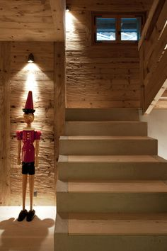 Concrete Staircase Wooden Steps And Wooden Pinocchio Sculpture Decoration Design Ideas: Warm And Cozy Chalet in Gstaad Interior With Rough Wood