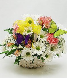 Our white wicker basket is filled with Fresh White Daisies, Babys Breath, Pink Carnations, Pink Lilies accented with sheer yellow ribbon and butterflies. Just like Mom picked them from the garden!
