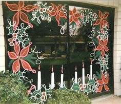Borders of poinsettia, holly, and candles dress up this set of sliding glass doors in elegant fashion. #windowpainting