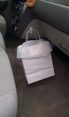 Use a Command Hook to keep a garbage bag from tipping over in the car - clever!  You can also use this for regular shopping bags or your purse!