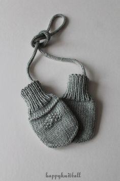 Knit thumbless baby mittens with cord
