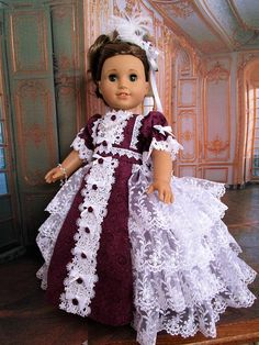 Regency ball gown in a rich burgundy cotton floral print. The fully lined bodice is decorated with lace, satin bows, hand stitched pearl beads delicate appliques and satin ribbon roses. The puff sleeves have elastic ruffles and lace. The high waisted lined skirt is decorated with a