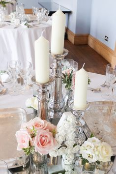romantic wedding flowers - silver candlesticks and small flowers with flowers