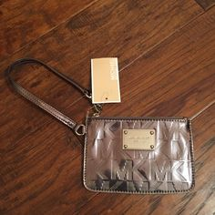 Michael Kors wristlet Small metallic mirror Michael Kors wristlet. Some discoloration on the back, as shown in the 3rd pic. Small scratch on the metal as shown in the 2nd pic. Nickel color. MICHAEL Michael Kors Bags Clutches & Wristlets