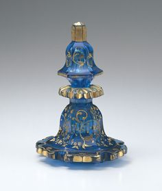 Bohemia 1830 H13.5cm This perfume bottle is a typical example of the Bohemian glasswork known as Biedermeier glass. Its lower part is spread out like a flared skirt and the shoulder and stopper are also similarly flared, with deep incisions added for decorative effect. Bohemian Glass | 19th century Perfume Bottle | Western Items | Museum | Takasago International Corporation