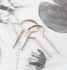 The shape reminds us of a keyhole, or a portal to another dimension. Measuring about an inch long, these easy-to-wear earrings slip through your lobes and hang steady. Hand-formed and hammered in our