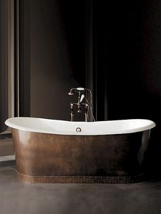 cast iron bathtub without tap holes with exterior covered in antiqued copper