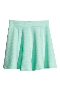 Falda corta con vuelo en punto con cintura elástica y cremallera visible en la parte trasera.