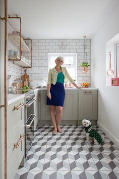 Aranżacja wąskiej kuchni z geometryczną podłogą i złotymi dodatkami