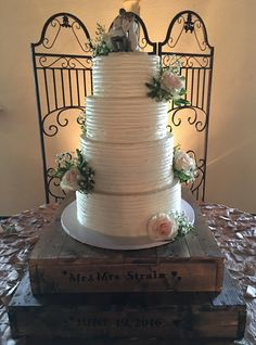 4-tier wedding cake with buttercream ribbon finish and fresh flowers for a Texas classic country wedding. Personalized and handmade cake stand also made by Confectionary Home.