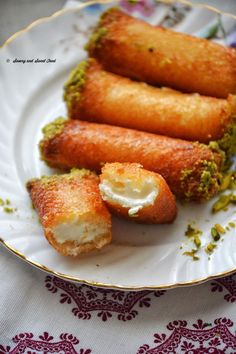 Znoud-el-Sit is a Lebanese dessert, made by rolling thick cream inside white bread, deep frying and then dipping these crispy rolls in a fragrant sugar syrup.