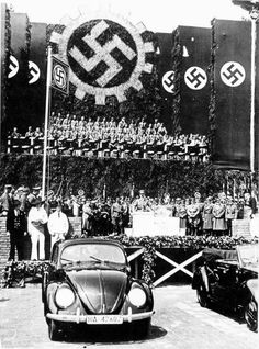 "Hitler presides over the launching of the Beetle. As the country ramped up for war, every German worker was required to put money aside every week for a Volkswagen or ""People's Car"", designed by Hitler with the help of Ferdinand Porsche. Millions of marks were collected by the Reich in this way, though not a single VW was ever delivered to a contributor. Hitler did present one to Eva Braun as a birthday present, though it's not certain that she ever learned to drive."