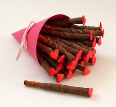 chocolate covered pretzels with a heart candy on top.