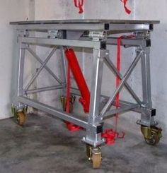Fold Up Welding Table - Homemade fold up welding table constructed from tubing, steel plate, C-channel, casters, steel pins, and a hydraulic cylinder.: