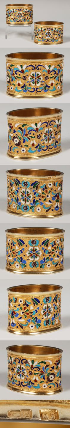 A pair of Russian silver gilt and enamel napkin rings, by Michael Zorin, Moscow, circa 1908-1917. Of oval form, the napkin rings decorated with scrolling floral and foliate motifs against a gilded stippled ground.