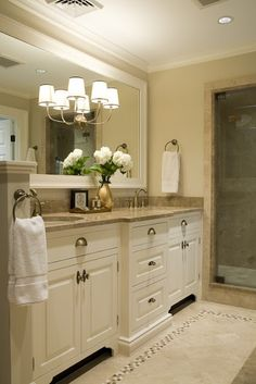Framed mirror with sconce(s); half wall at end of vanity; tile border on the floor