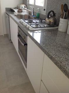 Reciclaje de cocina. Pisos porcellanato mate gris. Mueble termoformado blanco. Mesada y revestimientos granito gris mara.