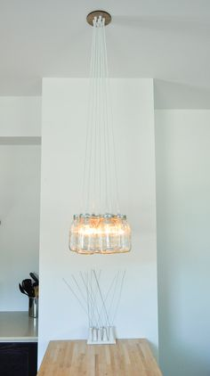 Mason Jar light fixture; think i may try something like this... cept drill holes in distressed wood, attach lids and electrical what nots, screw jars into lids... :-) replace the old ugly florecent fixture! (with energy saver bulbs, like the look of those better!)