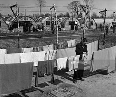 At Prisoner-of-War Camp 186 at Berechurch Hall, Colchester in Essex, a German prisoner of war hangs out his washing, whilst his compatriots play football.