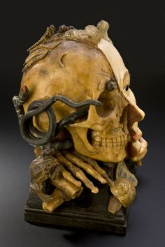"18th century wax vanitas model. Vanitas are works of art intended to remind the viewer of the shortness of human life, the uselessness of vanity and the certainty of death. This example features many symbols typical for this type of object, such as a skull and insects that feast on decaying flesh. The other side of the model shows the face during life. The verse scratched on to the front is from the biblical book of Ecclesiastes and reads ""vanity of vanities, all is vanity""."