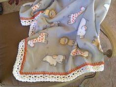 Soft gray, white Orange and yellow animal fleece baby blanket with a white and orange pretty crocheted edging. Blanket measures 31 x 40. This would be perfect for any baby boy. Blanket is machine washable and dryable