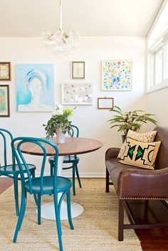 White dining space with small gallery wall and blue chairs