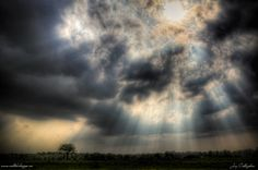 Caption: HDR shot of sun's rays shining through the clouds. Handheld shot, 3 consecutive images (+/- 3), converted to HDR