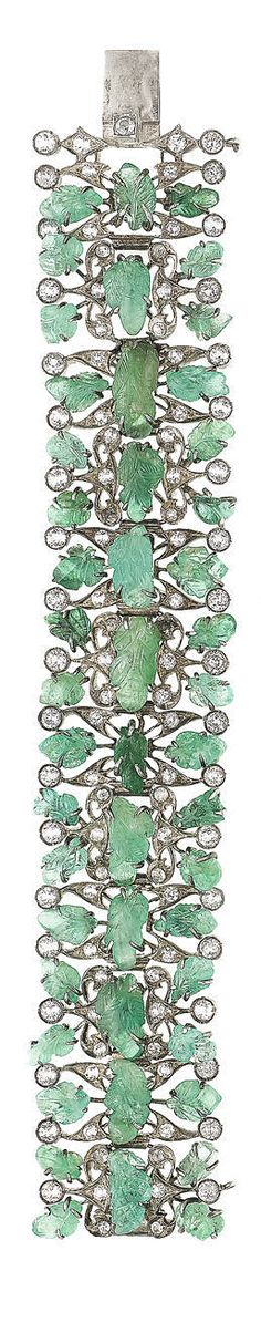An art deco, emerald and white sapphire bracelet, circa 1930. Composed of openwork articulated links set with carved emeralds of foliate design, interspersed with circular-cut white sapphires, length 17.5cm.