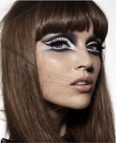 Mod style. Diffuse white eyeshadow with dramatic downward turned grey-black shadow line to bottom, cat eye and dramatic crease to top eye,