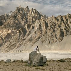Picture of young man checks his phone below the catherdral peaks of Tupopdan, Pakistan