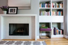 Very contemporary fireplace mantle and subtle tile surround in a monochromatic color palette.