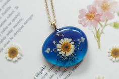 Nature inspired botanical necklace featuring chamomile and queen anne's lace encased in clear resin - made by FloralJoyJewelry