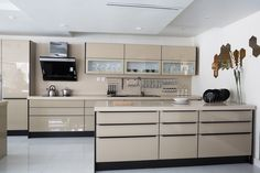 Polished tan modern kitchen with glass front cabinets, and white finish counter tops.