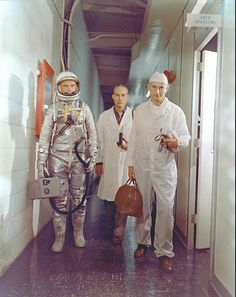 John Glenn, Mercury -- February 1962 by NASA ,Astronaut John H. Glenn Jr., NASA flight surgeon William Douglas and equipment specialist Joseph W. Schmidt leave crew quarters prior to the Mercury-Atlas 6 mission. Glenn is in his pressure suit and is carrying the portable ventilation unit.
