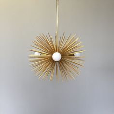 VIDEO: https://vine.co/v/MOptV2PWzbV  This gold urchin pendant is MADE TO ORDER with a typical lead time of 4 weeks. Fixture lead time can be decreased to 1 week via the following listing: https://www.etsy.com/listing/166962547.  Measurements: - Diameter: 15 in - Height: 12 in - Weight: 5 lbs  Features: - Hundreds of metal spines - Three candelabra-base (E12) light sockets - Brass plated finishes Fixture Includes: - Simple matching canopy set - 6-ft electrical cord configured to be…