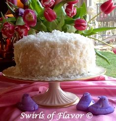 Moist layers of coconut cake topped with coconut buttercream frosting and flaked coconut surround a tangy lemon filling making every bite a taste of heaven!