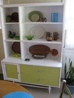This was American made and very damaged veneer. Also my kitchen is small and the dark wood took up too much visual space so I gave it an update. New paint and knobs.Displayed are warm teak trays and housewares for Fall and various greens.