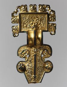 Square-Headed Brooch, 6th century  Anglo-Saxon  Copper alloy with gilding and niello inlay.  This large gilded brooch, which would have been used to secure a cloak, displays the Anglo-Saxon preference for lavish decoration with a particular emphasis on fantastic animal forms. Dark strips of niello inlay frame its richly faceted surface, which is further animated by beast heads, many with bird beaks, projecting from the edges.
