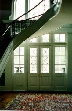 Back entry graced by spiral stair case that envelops the leaded glass French doors which feature custom lead castings and double vaulted eight foot transoms that also features custom lead castings