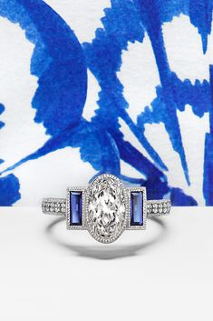 Something new, something blue... Create your very own engagement ring with our help! Get inspired by this beautiful custom ring with an oval centre diamond, baguette blue sapphires and bead-set diamond band with milgrain set in platinum.