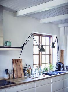 Белая кухня с лампами и столешницами.