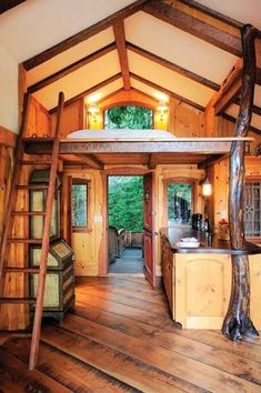 This organic-looking tiny cabin boasts a tree trunk holding up part of the sleeping loft. | Tiny Homes