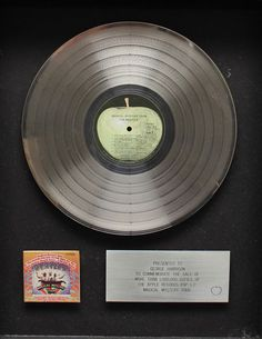 Beatles memorabilia: The Beatles Magical Mystery Tour Platinum disc presented to George Harrison. Beatles memorabilia: The Beatles Magical Mystery Tour Platinum disc presented to George Harrison. The framed platinum album disc mounted above a reduction of the front cover beside a plaque engraved reading 'PRESENTED TO GEORGE HARRISON TO COMMEMORATE THE SALE OF MORE THAN 1,000,000 COPIES OF THE APPLE RECORDS POP L.P. MAGICAL MYSTERY TOUR' with the apple records logo to the bottom left. The ...