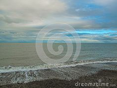 The broken sky of the coast of Bray, County Wicklow, Ireland. And the water recedes out in the dark green Irish Sea. With grey clouds broken by bright blue sky.