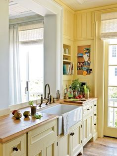 Buttery walls and cabinets paired with butcher-block countertops add beach-cottage charm at a good price in this kitchen in Seaside, Florida.
